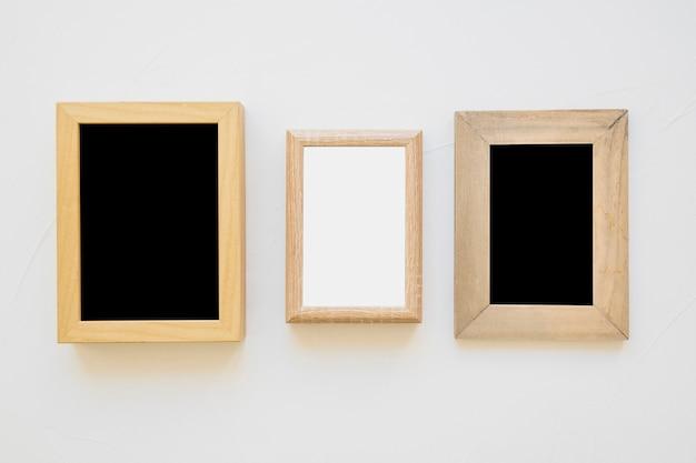 Biała ramka między czarnymi ramkami na ścianie
