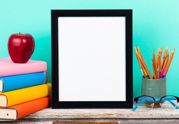 Biała ramka na stole lub biurku ze stosu książek