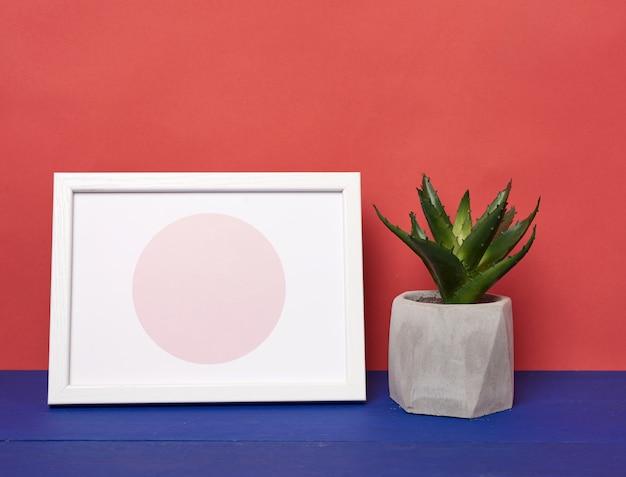 Biała ramka na zdjęcia i doniczka ceramiczna z rosnącą rośliną na niebieskim drewnianym stole