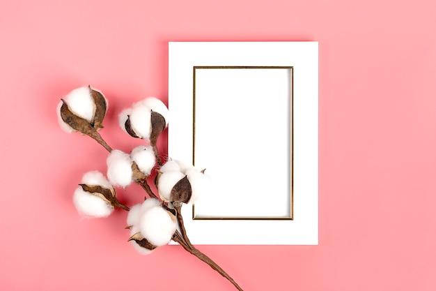 Biała ramka na zdjęcia i gałązka bawełny na różowym tle