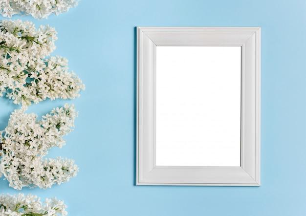 Biała ramka na zdjęcia i kwiaty bzu na niebieskiej ścianie.