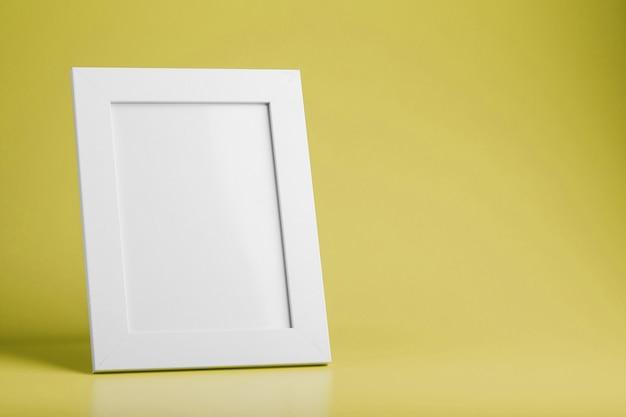 Biała ramka na zdjęcia na żółtej powierzchni