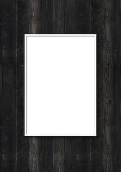 Biała ramka na zdjęcia wisząca na czarnej drewnianej ścianie