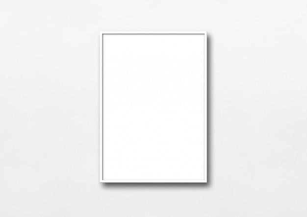 Biała ramka na zdjęcia wisząca na ścianie. pusty szablon makiety