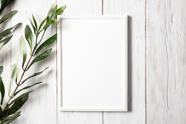 Biała ramka na zdjęcia z gałązką eukaliptusa na białym drewnianym stole