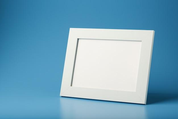 Biała ramka na zdjęcia z pustą przestrzenią na niebieskim tle.