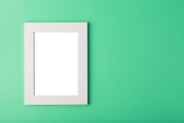 Biała ramka na zdjęcia z pustą przestrzenią na zielonym tle.