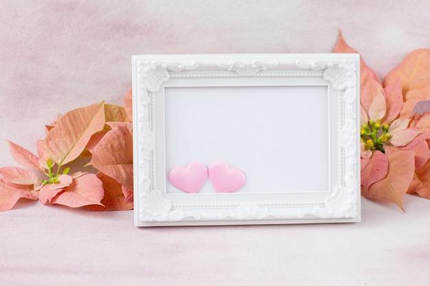 Biała ramka na zdjęcia z różowymi sercami, różową poinsecją