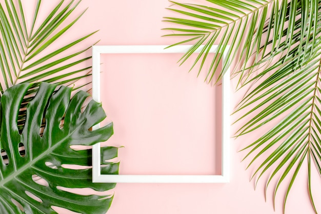 Biała ramka ozdobiona tropikalnymi liśćmi na różowym tle