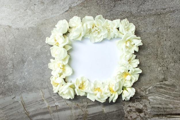 Biała ramka pusta, płatki spa lub wesele makieta szare tło widok z góry. piękny kwiatowy