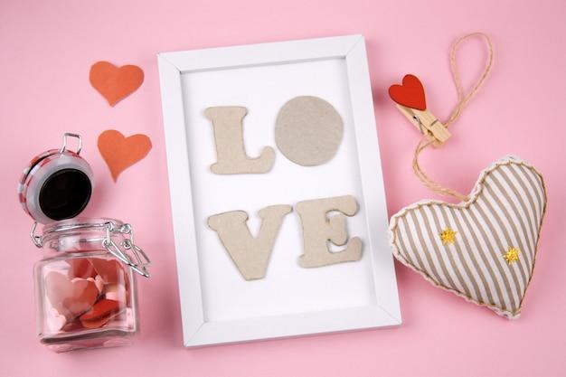 Biała ramka z literami miłość, czerwone serce i słoik z sercami na pastelowym różowym tle