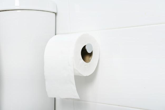 Biała rolka miękkiego papieru toaletowego starannie zawieszona na chromowanym uchwycie na białej ścianie łazienki. ścieśniać