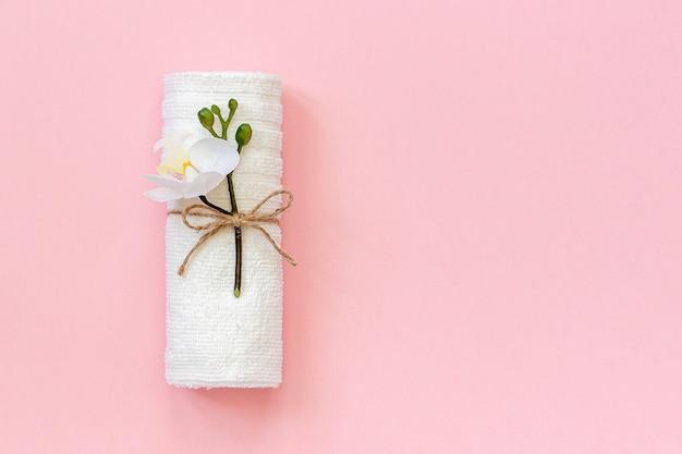 Biała rolka na ręczniki wiązana liną z gałązką kwiatu orchidei na różowym papierze.
