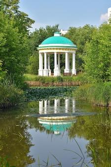 Biała rotunda w parku, odbicie rotundy w wodzie, widok rotundy przez drzewa w parku, rotunda w letnim słońcu