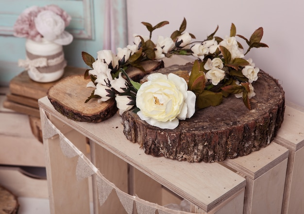 Biała róża na drewnianym talerzu na drewnianym pudełku
