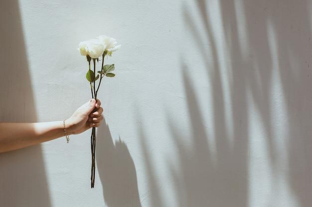 Biała róża w dłoni z szarymi betonowymi ścianami z szalami