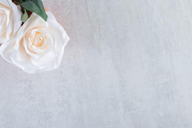 Biała róża w misce, na białym stole.