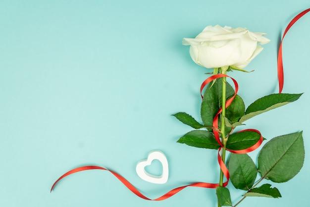 Biała róża z czerwoną satynową wstążką i czerwonymi drewnianymi serduszkami na jasnoniebieskim tle. widok z góry