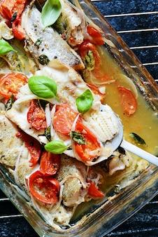Biała ryba (mintaja, dorsza, morszczuka) zapiekana z pomidorami, włoskimi ziołami i świeżymi liśćmi bazylii w bazylii we własnym soku. pyszna śródziemnomorska kolacja z owocami morza.