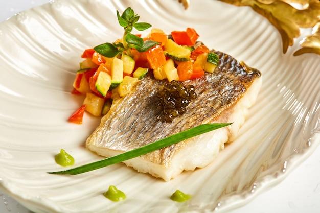 Biała ryba na talerzu z warzywami i dekorowanym czarnym kawiorem. koszerne jedzenie.