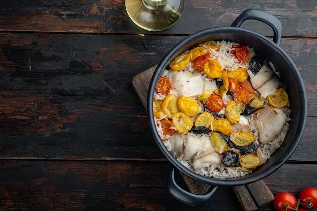 Biała ryba tilapia z ryżem basmati i pomidorkami koktajlowymi na ciemnym drewnie