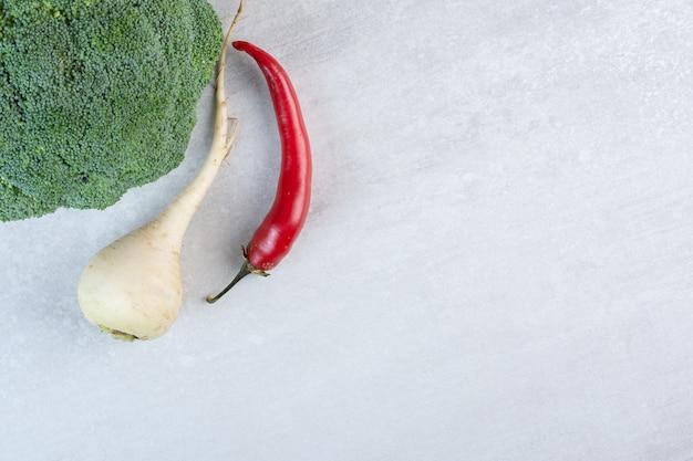 Biała rzepa, brokuły i papryczka chili na kamiennej powierzchni. wysokiej jakości zdjęcie