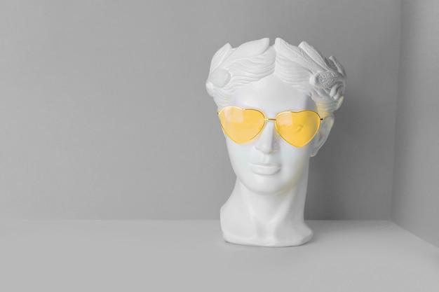 Biała rzeźba antycznej głowy w żółtych okularach z sercami. na geometrycznym tle w dwóch kolorach.