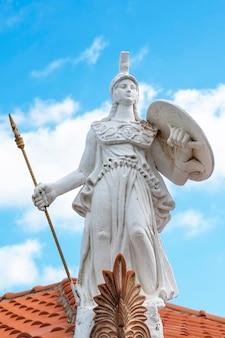 Biała rzeźba wykonana z kamienia w stylu antycznej grecji, wojownika znajdującego się na krawędzi dachu budynku w grecji