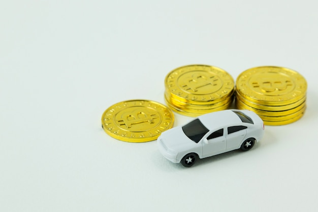 Biała samochód zabawka i złocista moneta na białym tle.