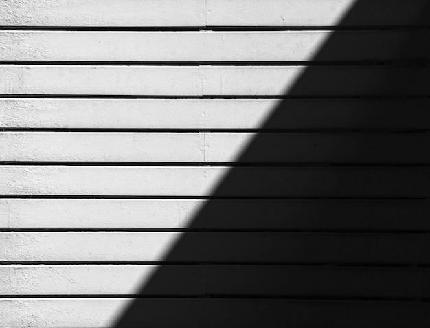 Biała ściana drewnianych listew ze światłem i cieniami
