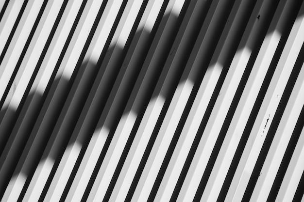 Biała ściana stalowych listew ze światłem i cieniami