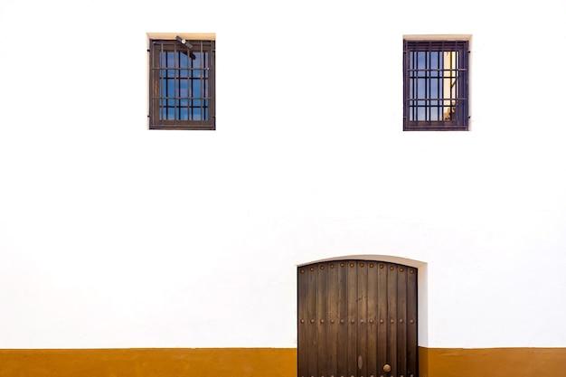 Biała ściana z drzwiami i dwoma oknami w kształcie twarzy.