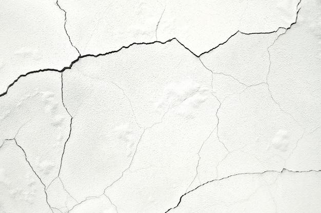Biała ściana z uszkodzonym tynkiem
