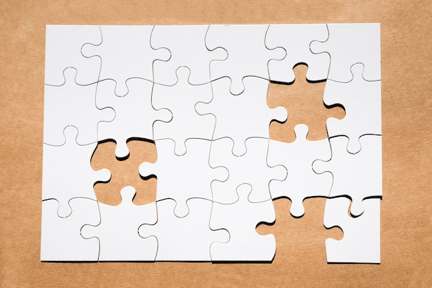 Biała siatka układanki z brakującym elementem układanki na brązowym papierze teksturowanej