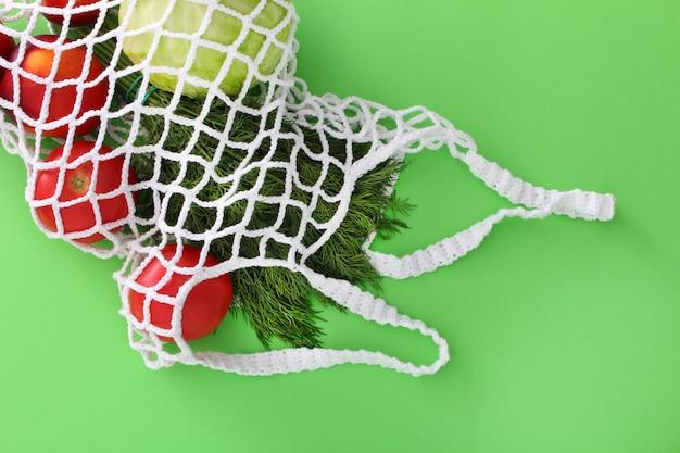 Biała siatkowa torba na zakupy wielokrotnego użytku z owocami i warzywami: pomidorami, kapustą, burakami, koperkiem, brzoskwiniami.