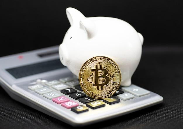 Biała skarbonka i gole bitcoin stoją na kalkulatorze i czarnym tle. to dla koncepcji oszczędzania pieniędzy i zachowania waluty kryptograficznej.