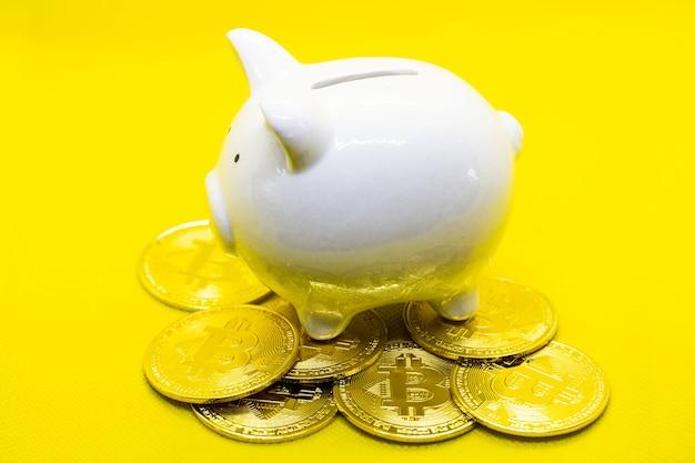 Biała skarbonka leżała na wielu złotych bitcoinach na czarnym tle. do oszczędzania bogactwa pieniędzy i koncepcji finansów oraz miejsca na projekt.