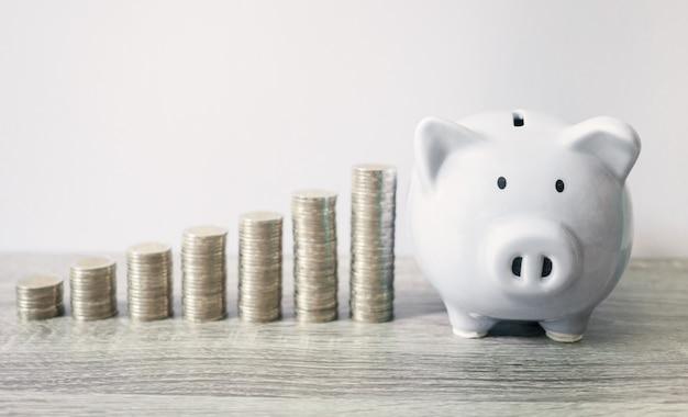 Biała skarbonka z wykresem wzrostu monet, oszczędzając pieniądze na przyszły plan i koncepcję funduszu emerytalnego