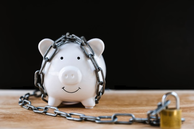 Biała skarbonka zablokowana, przykuta czarnym tłem, chroń oszczędności, chroń kapitał, chroń koncepcję funduszu emerytalnego.