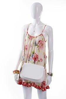 Biała skórzana torebka na manekinie. żeński manekin sobie prostą torebkę. kwiatowy sarafan i biała torba. letnia odzież z dodatkami na nadgarstki.