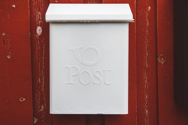 Biała skrzynka pocztowa na czerwonej drewnianej ścianie z czerwonymi drzwiami.