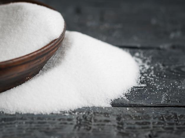 Biała sól, drobno zmielona, wylana z glinianej miski na drewnianym stole