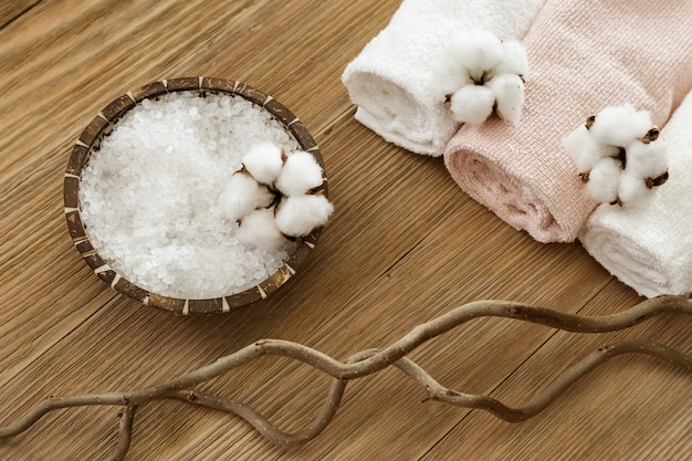 Biała sól morska w misce z naturalnego kokosa i puszystych kwiatów bawełny oraz zrolowanych ręczników na starej drewnianej powierzchni. martwa natura dla koncepcji spa. skopiuj przestrzeń i widok z góry.