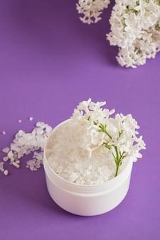 Biała sól morska w plastikowym słoiku i białe kwiaty bzu na tle bzu naturalna koncepcja kosmetyczna do pielęgnacji ciała