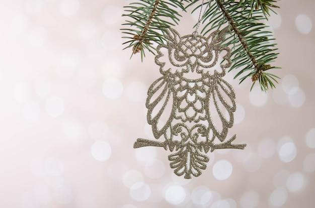 Biała sowa zabawka wisi na gałęzi choinki. bokeh. dekoracja świąteczna