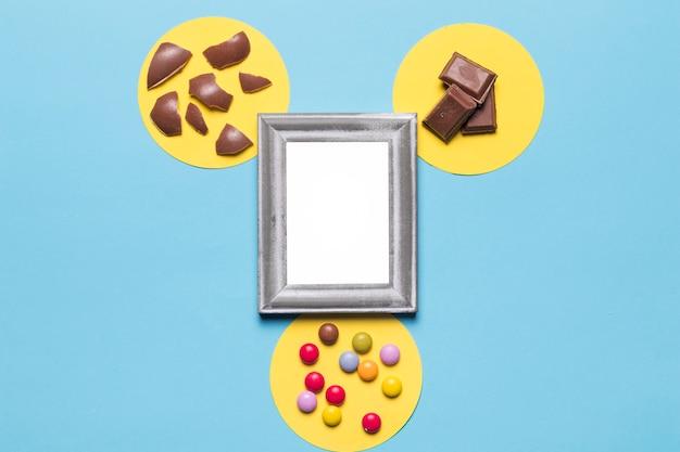 Biała srebrna rama nad żółtą okrągłą ramą z cukierkami; kawałki czekolady i skorupki jaja wielkanocne na niebieskim tle