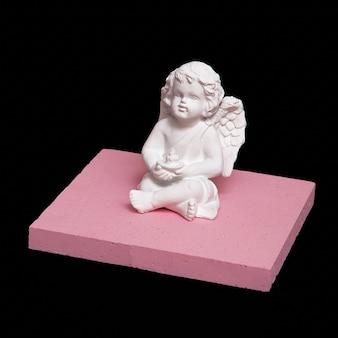 Biała statua anioła w przestrzeni czarnej geometrii. minimalna sztuka twórcza