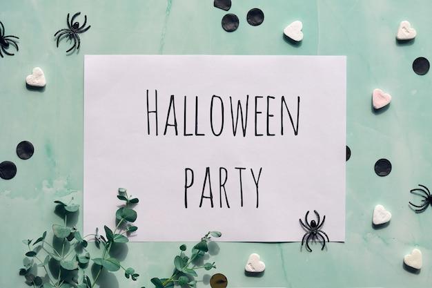 Biała strona z tekstem halloween party na miętowym zielonym tle kamienia.