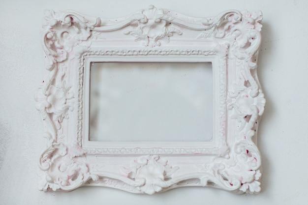 Biała stylowa barokowa rama z miejscem na kopię na białym tle na widok z boku białej ściany