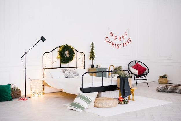 Biała stylowa przytulna sypialnia w stylu skandynawskim. świąteczne dekoracje świąteczne: choinka, wieniec, girlandy led.